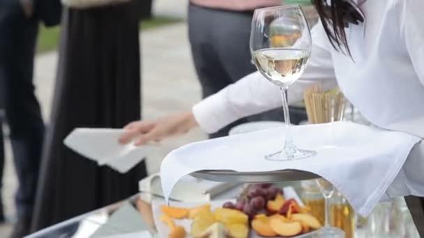Číšník drží tác se sklenkou vína
