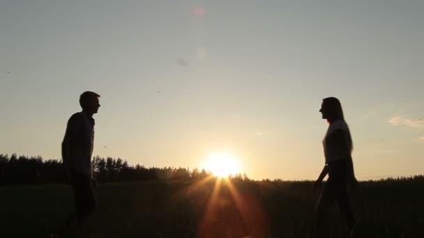 Guy dívka setkají v poli při západu slunce