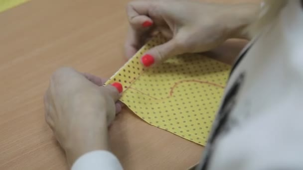 The girl sews by hand a needle and a red thread