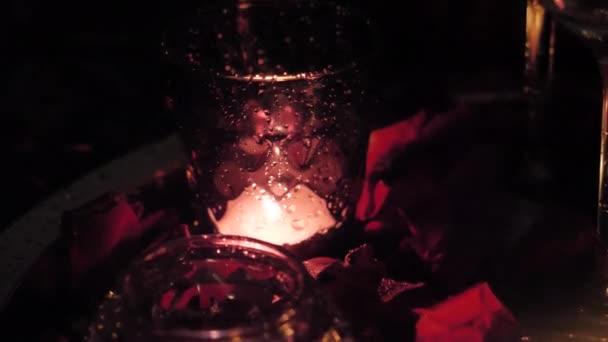 Un vetro con una candela intorno i petali di rosa