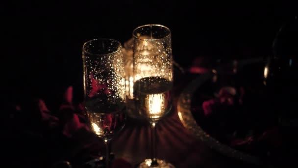 Gläser mit Champagner, brennende Kerze, Rosenblätter