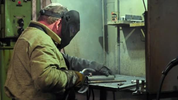 Průmyslový pracovník v ochranné masce s použitím moderního svařovacího stroje pro svařování kovů na výrobu