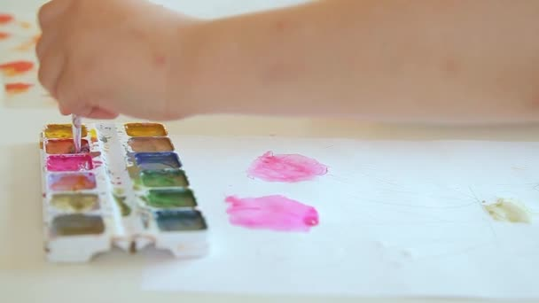 The childrens hand of the artist picks up paint on the brush.