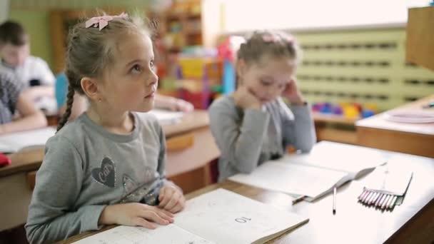Dvojčata sedí u stolu ve třídě školky. Děti ve škole sedí u stolů.
