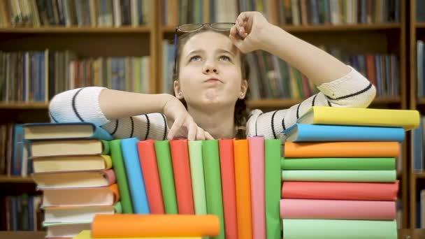 Mädchen mit Büchern in der Bibliothek hat eine neue Idee.
