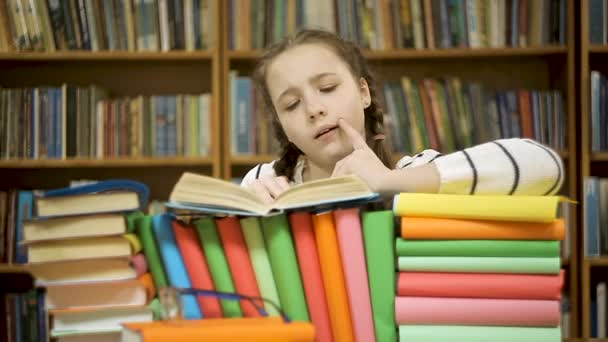 Girl is not interested in reading a book. The child chooses to play a gadget than to read a book