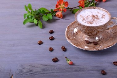 Freshly brewed coffee with milky foam topped with cinnamon in a cup against the gray wooden background