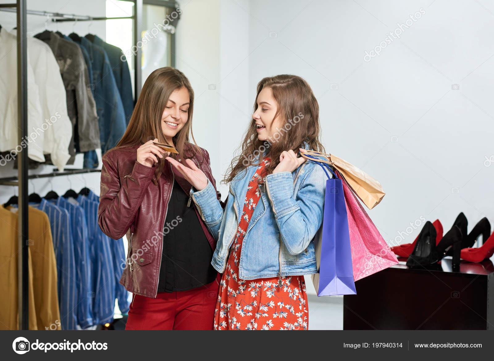 f783ef7044 Chicas comprando ropa en tiendas en el centro comercial– imagen de stock
