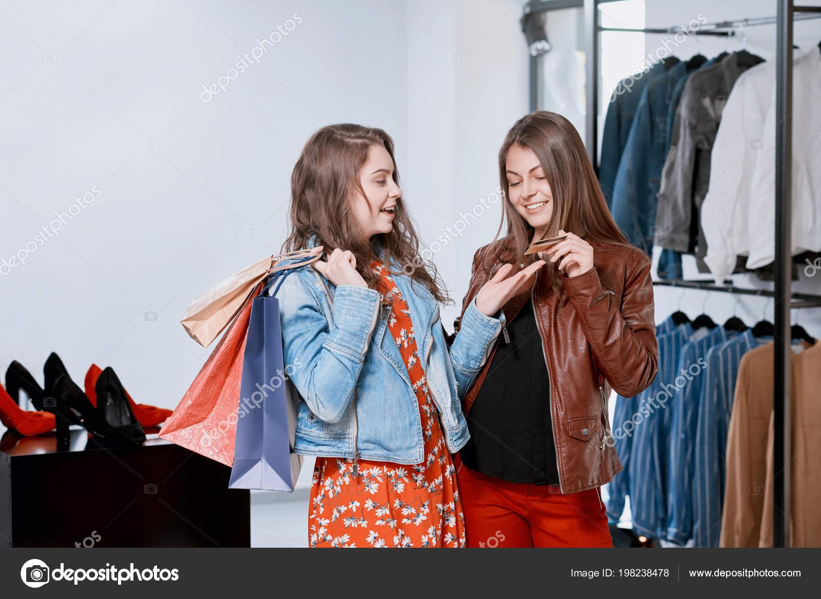 f4e790d3cb FrontView de chicas comprando ropa en tiendas en el centro comercial — Foto  de Stock
