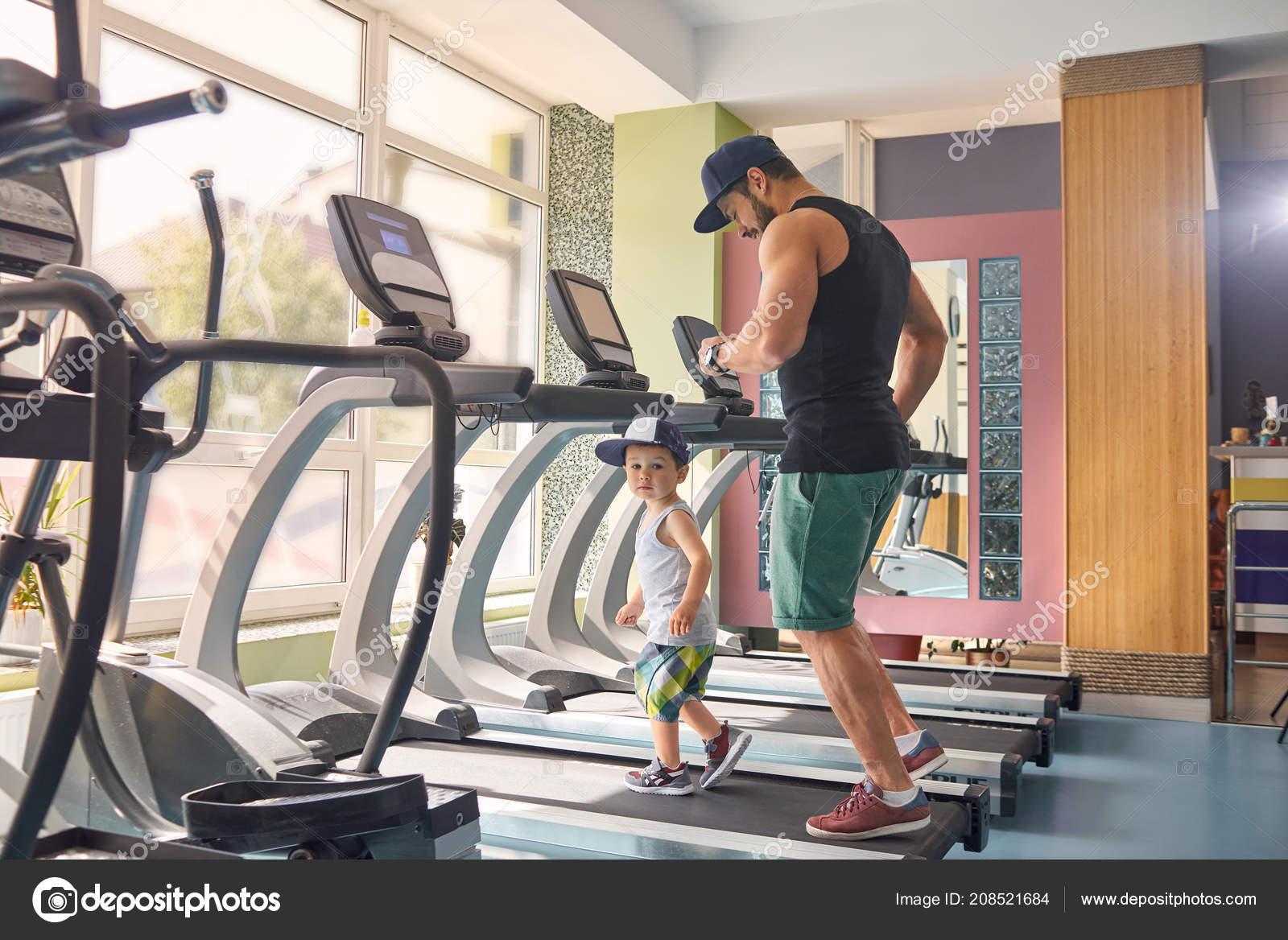 Circuito Gimnasio : Joven padre corriendo en circuito en el gimnasio con su pequeño