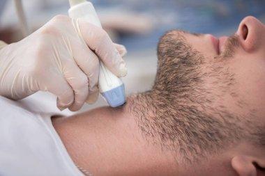 Crop of male patient on ultrasound diagnostics.