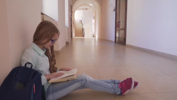Girl in glasses sitting on floor and preparing to lesson