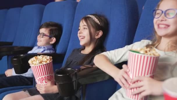 Gruppe lächelnder Kinder sitzt im bequemen Stuhl im Kino