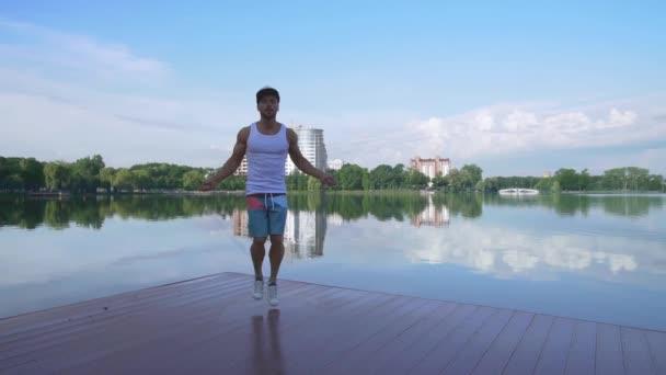 Schöner Sportler trainiert auf Seebrücke mit Springseil