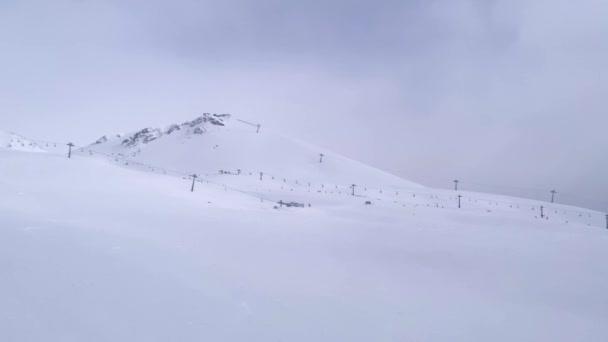 Nerozpoznatelní lyžaři jedoucí ze zasněženého kopce.