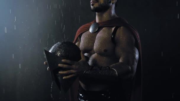 Nerozpoznatelný spartan při pohledu na kapky deště na helmě.