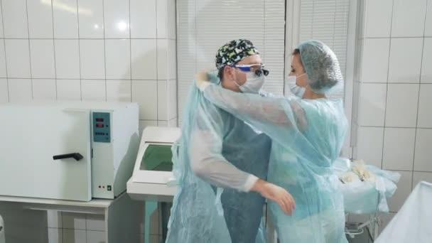 Chirurgii v nemocnici. Lékaři se připravují na operaci, sestra pomáhá chirurg se do provozu. Žena pomáhá lékaře lékařské rukavice. Ten muž má na sobě provozní šaty