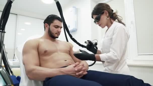 Doktor kosmetička v speciální brýle a rukavice, klade gel na těle pacientů. V kosmetice odstraní srst na těle pomocí laserové odstranění rozšířených žilek na přístroji. Pacient nemá