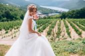 Fényképek A menyasszony nevet, és örül a napsütéses nap. A lány egy elegáns csokor virágot tart a kezében, és sétál, szőlőskertek, mezők és dombok között. Ő csodálja a kék-tó