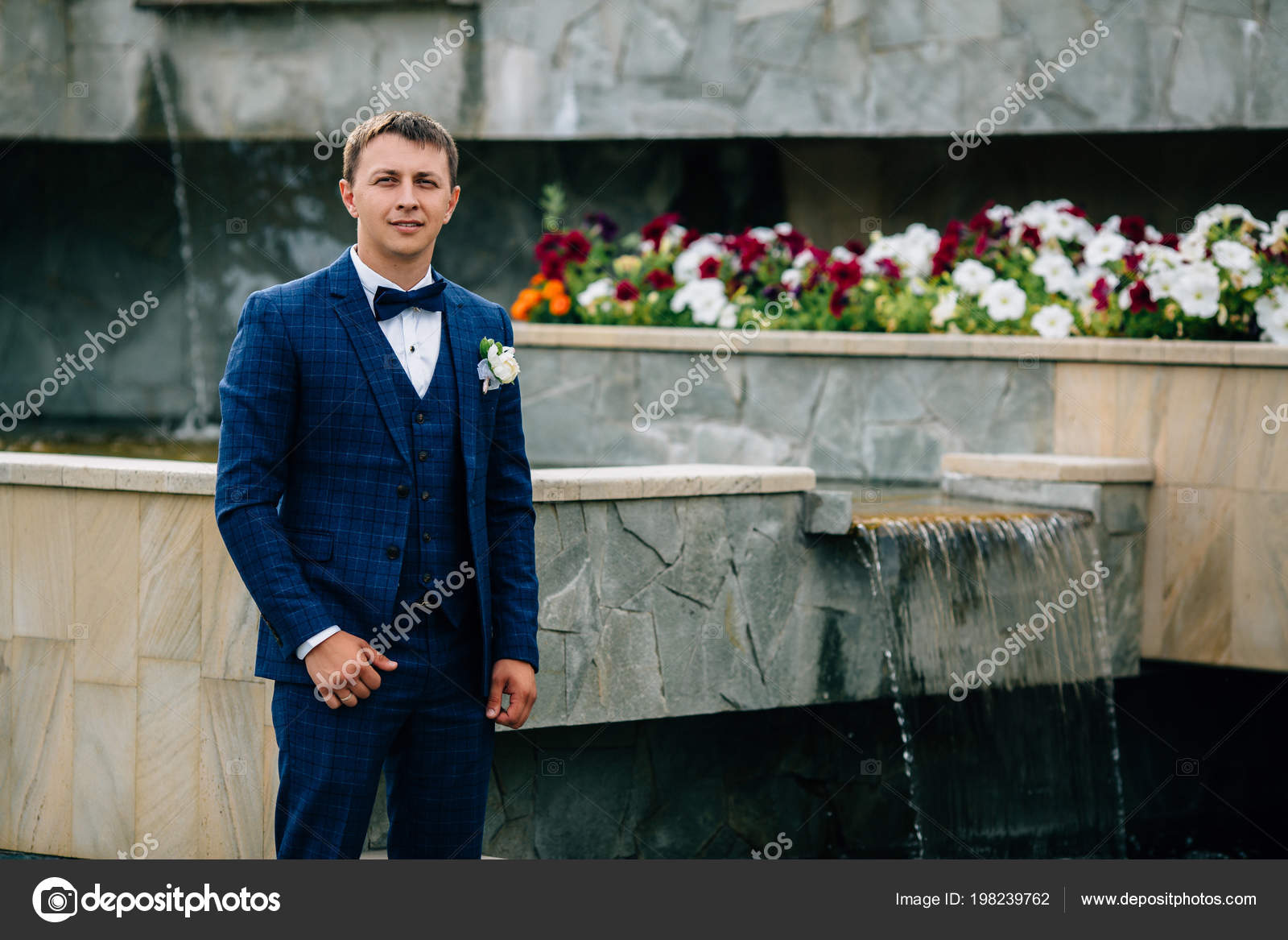 A Stylish Guy With A Bow Tie And A Buttonhole Poses Near An