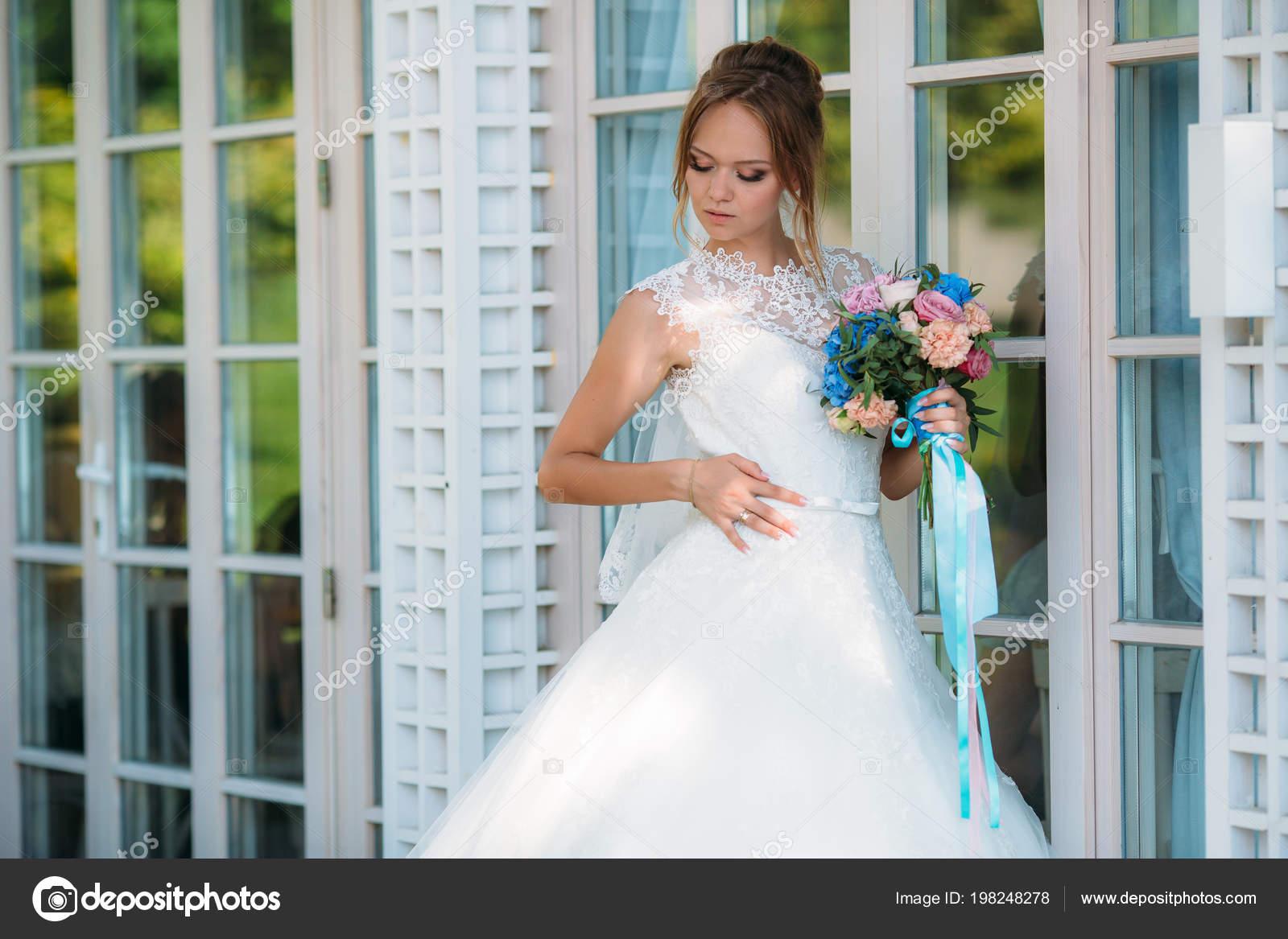 efb95de12b71 La sposa bionda ammira il suo abito da sposa bianco pizzo
