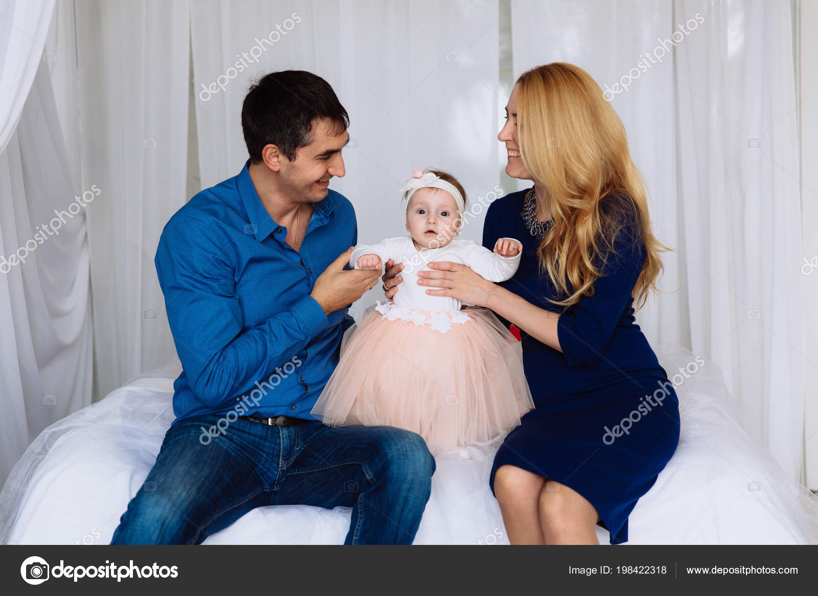 Mom Dad And A One Year Old Girl Between Them Gazes Intently At The