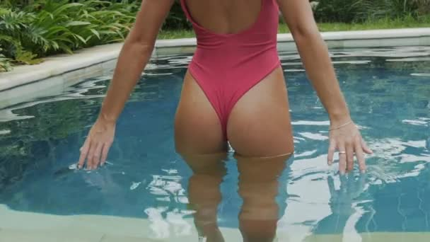 Close-up of a round luscious beautiful attractive ass young girl in a swimsuit. The model stands in the pool, the rear view, the slow-motion shot cropped frame stands, the girl drops her fingers into