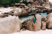 Tajné beach v tropické zemi, na ostrově, kde neexistují žádné cizinci, krásná štíhlá dívka spočívá a těší se krásou skal a modré moře