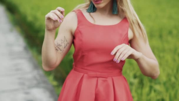Close-up of a cropped frame of a blonde girl with about sporting hands in a bright dress gently and gracefully moves her hands and fingers to the music in a slow-motion shot. Graceful dance of a