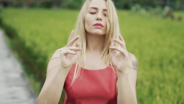 A blonde with beautiful lips and long hair dances outside, gently moves the body, hands, hands and fingers, sensually dances in a slow-motion shot. The concept of body language, sensuality, dance.