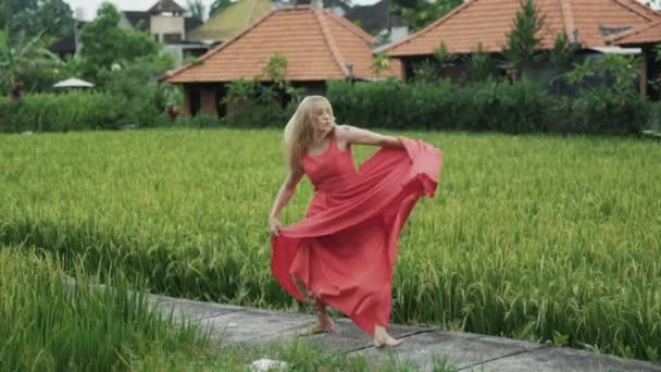 A graceful slender graceful girl with a beautiful figure is spinning in a silk soaring airy red long dress, dancing, wriggling, enjoying her movements, slow-motion shooting.
