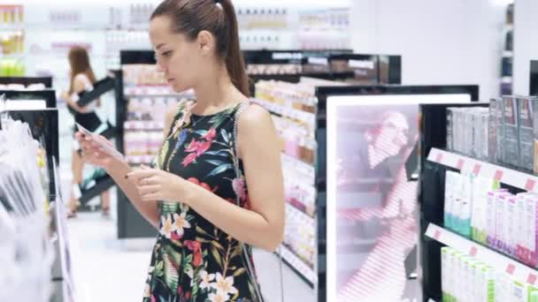 A close-up of a girl goes to the perfume and cosmetics store, chooses a make-up remover, reads labels on bottles, chooses a suitable brand. The concept of beauty, shopping.