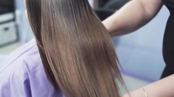 Zpomalené střílení detail dlouhé tmavé vlasy mladé dívky. Brilantní a hebké vlasy po narovnání keratin. Efekt keratinu, rovné vlasy. Koncept salony krásy, krása.