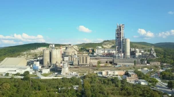 Luftaufnahme einer Zementfabrik, eines großen Industriegebäudes in den Bergen. Konzept der Zisternen, Rohre, Metallkonstruktionen, Betonproduktion. Tagsüber Filmaufnahmen mit einem schönen blauen Himmel.