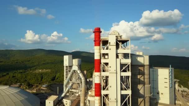 Letecký pohled na cementárna, velké průmyslové budově v horách. Koncept cisterny, potrubí, kovových konstrukcí, konkrétní výrobní. Denní záběry s krásnou modrou oblohu.