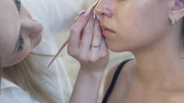 Detail oříznuté rám, Zpomalený záběr, make-up pečlivě maluje oční linky s oční linky, vizuálně otevře modely vypadají s pomocí oční linky. Make-upovými umělci pracují koncept, make-up