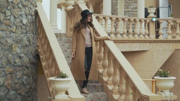 Close-up an attractive brunette has a European appearance, made curls of her long hair, casual makeup, put on a long coat and hat, goes down the steps, looks around, smiles.