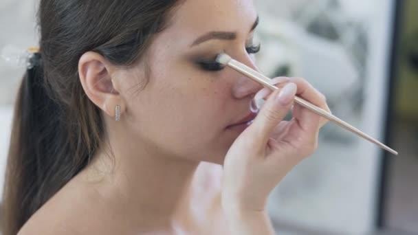Detail steadicam, tvář krásná mladá brunetka se zavřenýma očima, make-up dělá její oční make-up, kreslí stín na horním víčku, směsi. Pojetí krásy, make-up