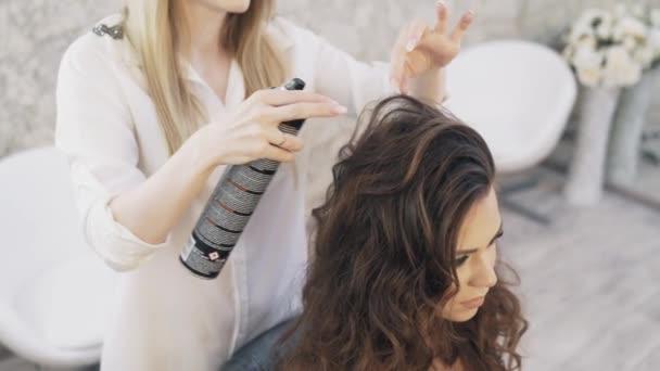 Pohled shora zpomalené, detail, kadeřnice dělá styl jeho klienta, vyloží každý pramen vlasů a řeší s lak, deale krásný účes. Pojem lidí, salony krásy, make-up.