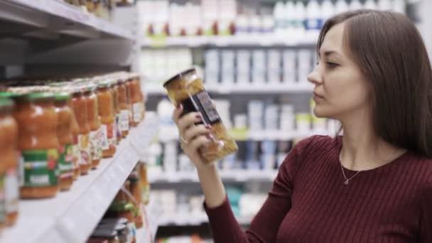Mladá hospodyňka vybrala konzervované houby v obchodě