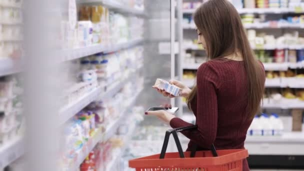 Young girl with a phone and a grocery basket in her hand chooses products in store.
