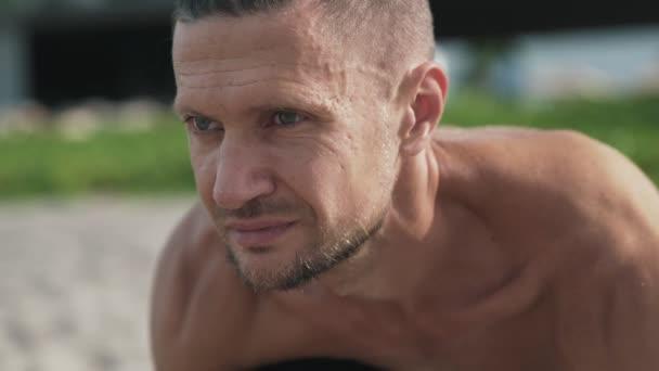 Zblízka portrétní shirtless chlap stojící jóga představuje, s úsměvem a relaxaci na pláži