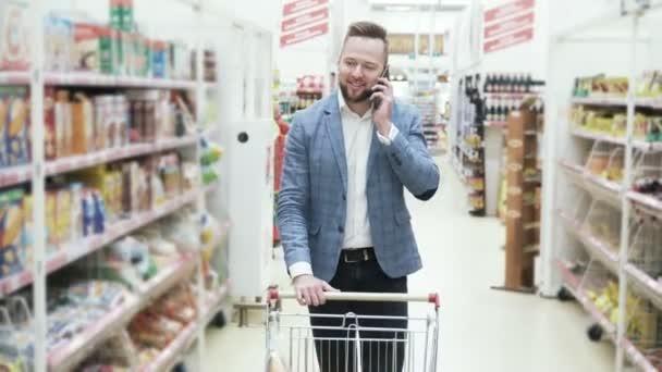 Mladý usmívající se muž v bílé košili se mluví na smartphone a procházky mezi regály s zboží v supermarketu, steadicam shot