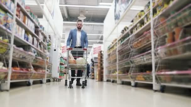 Man rolls trolley with foods beetwen shelves and choose products in supermarket, steadicam shot.