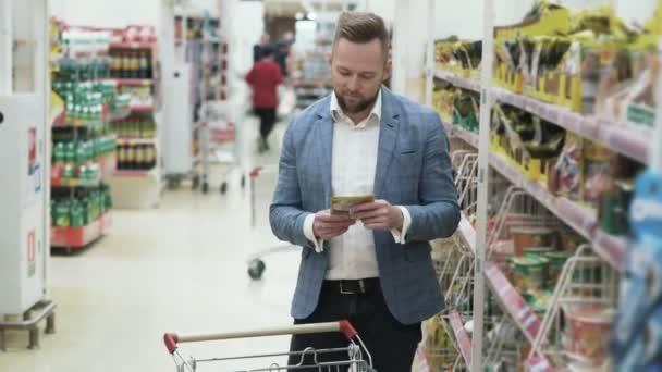 Šťastný mladý usmívající se pár výběrem potravin a Nakupování v supermarketu