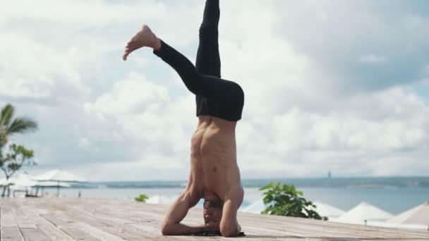 Člověk dělá cvičení jógy s stoj na krásné pláži
