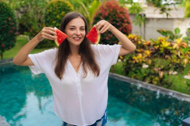 Portrait of attractive girl in white shirt holds two slices of watermelon near her face