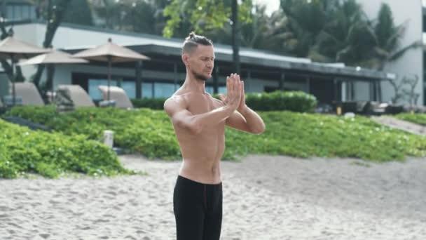 Sportovní muž dělá jógu dechová cvičení s rukama dohromady a oči zavřené.