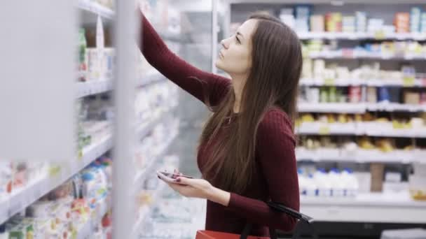 Beautiful girl with red basket choosing yogurt in grocery section at supermarket