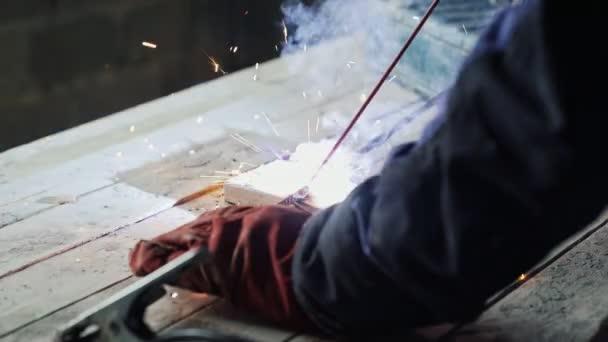 Detail svářeč svařuje dvě kovové části. Dělník v kombinéze pracuje doma. Bright jiskry z kovu. Koncept manuální práce, rozvoj, inženýr, kovozpracující průmysl
